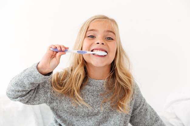 Ritratto del primo piano del bambino sveglio in pigiama grigio che pulisce i suoi denti