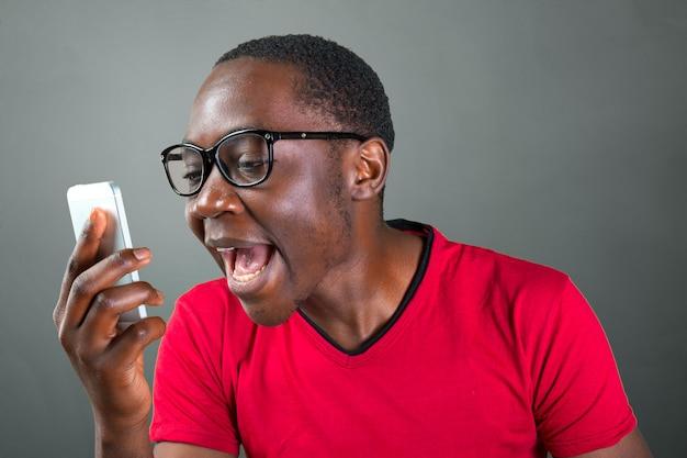 Ritratto del primo piano del giovane bello arrabbiato, tipo, incazzato studente, operaio pazzo, impiegato, cliente insoddisfatto, gridando mentre sul telefono