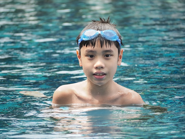 Ritratto del primo piano del ragazzo sveglio nella piscina