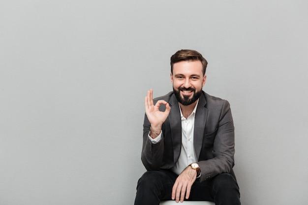 Ritratto del primo piano del tipo allegro che mostra segno giusto mentre riposando sulla sedia in ufficio che è soddisfatto, isolato sopra grey