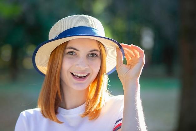 Ritratto del primo piano dell'adolescente dei pantaloni a vita bassa della testarossa in cappello giallo che sorride all'aperto nel parco soleggiato di estate.