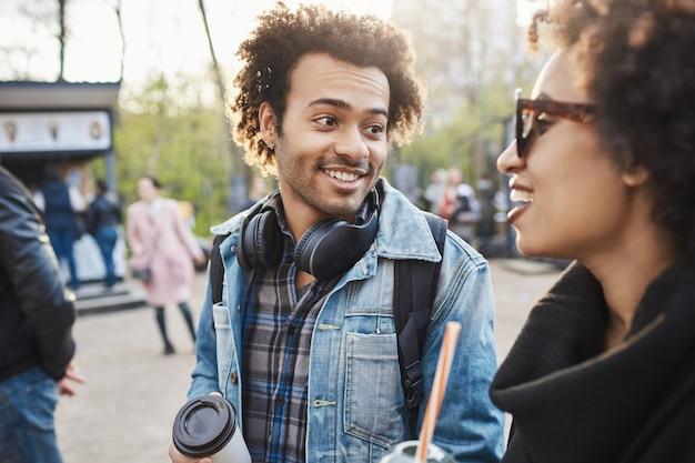 Ritratto del primo piano dell'afroamericano alla moda con un sorriso carino e acconciatura afro parlando con i fratelli mentre si diverte nel parco, beve caffè e scherza.