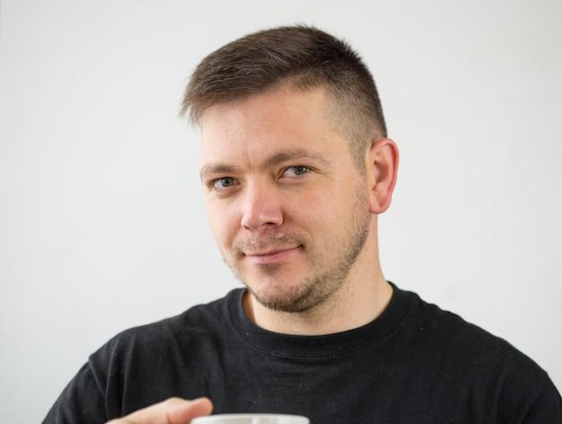 Ritratto del primo piano dell'uomo bianco caucasico serio di 30 anni su fondo bianco in maglietta e tazza di caffè nere. uomo moderno astuto felice sicuro che guarda in camera. stile di vita. spazio per il testo.