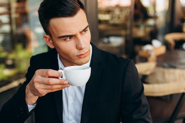 Ritratto del primo piano dell'uomo d'affari che tiene una tazza di caffè e che guarda lateralmente - immagine
