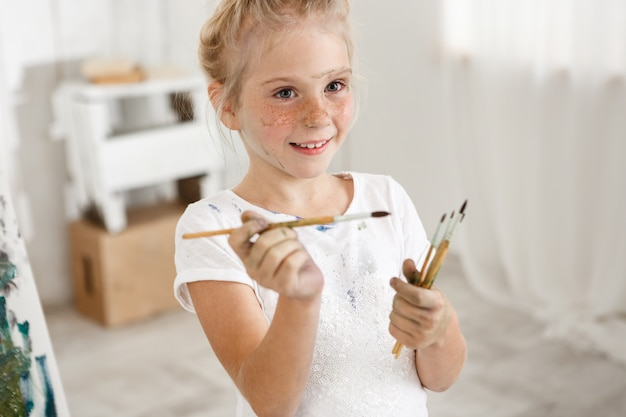 Ritratto del primo piano della bambina europea sveglia bionda con vernice sul suo fronte lentigginoso e panino dei capelli che sorride con tutti i suoi denti che tengono un mazzo di spazzole in sue mani. la ragazza allegra ha incasinato il suo bianco