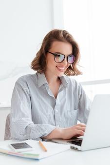 Ritratto del primo piano della donna allegra della lunetta in vetri facendo uso del computer portatile mentre lavorando a casa