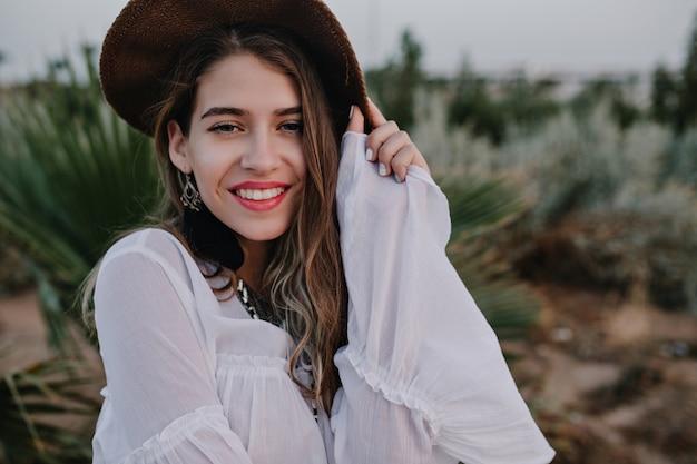 Ritratto del primo piano della donna attraente in cappello marrone e camicetta bianca in posa con un sorriso carino. la bella giovane donna senza trucco che trascorre il tempo fuori gode della vista della natura e della sera