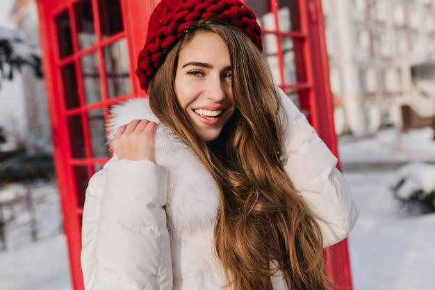 Ritratto del primo piano della donna felice con capelli castani lucidi che posano accanto alla cabina telefonica rossa. foto all'aperto di una splendida modella in berretto lavorato a maglia che si gode la gelida mattina in inghilterra.