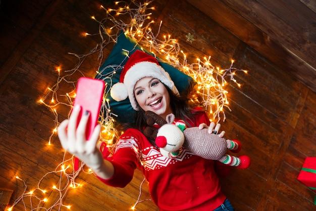 Ritratto del primo piano della donna in cappello di santa avvolto nelle luci di natale che prendono selfie e che si trovano sul pavimento di legno a casa