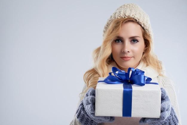 Ritratto del primo piano della donna sbalorditiva che tiene il presente del nuovo anno