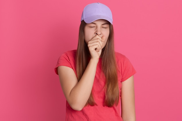 Ritratto del primo piano della donna stanca che sbadiglia che copre la bocca con il pugno, sembra esausto, indossa maglietta e berretto da baseball,