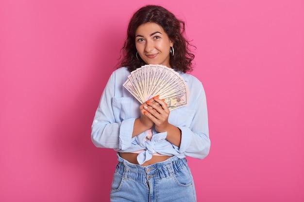 Ritratto del primo piano della giovane donna che tiene mazzo di soldi in mani che sono felici, esprimendo felicità, celebrando la sua conquista.