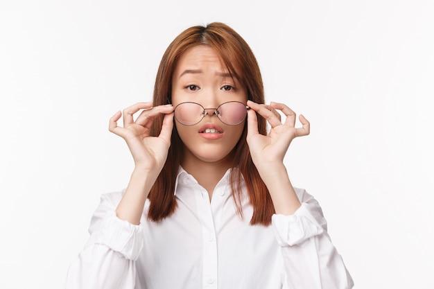 Ritratto del primo piano della ragazza asiatica carina confusa e incerta che toglie gli occhiali e che sembra incerta, non posso vedere in occhiali prescritti con lenti che non si adattano, in piedi sul muro bianco senza tracce