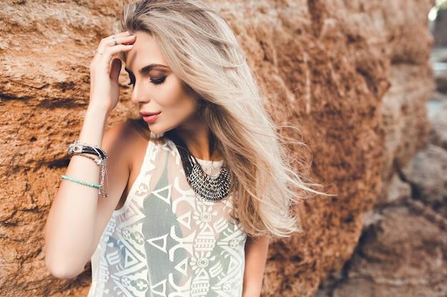 Ritratto del primo piano della ragazza bionda con capelli lunghi che posano alla macchina fotografica su fondo di pietra. tiene gli occhi chiusi.