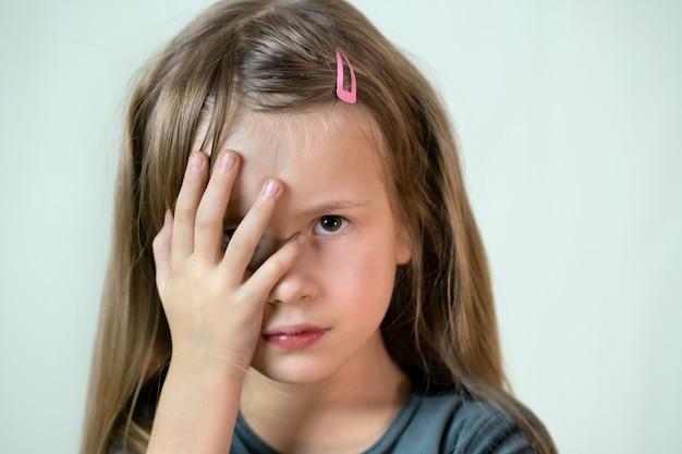 Ritratto del primo piano della ragazza del piccolo bambino con capelli lunghi che coprono la sua bocca di mani.