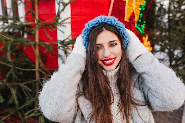 Ritratto del primo piano della ragazza entusiasta in cappello blu che posa con l'espressione del fronte felice davanti agli alberi di natale. foto all'aperto di donna affascinante con i capelli scuri in piedi vicino alla decorazione del nuovo anno.