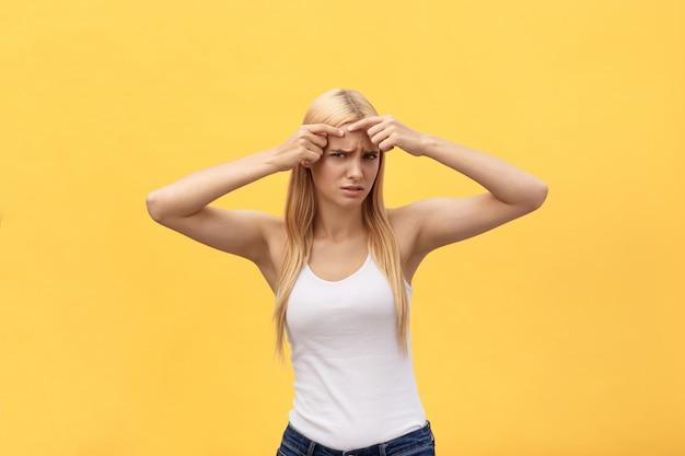 Ritratto del primo piano della ragazza preoccupata con il problema dell'acne, toccando fronte, stazione termale, terapia, trattamento, isolato sopra fondo giallo