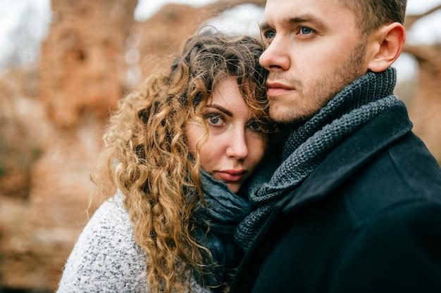 Ritratto del primo piano delle coppie amorose. due amanti in piedi all'aperto guancia a guancia. uomo con abbracci donna. maschio e femmina che si godono nelle rovine del castello