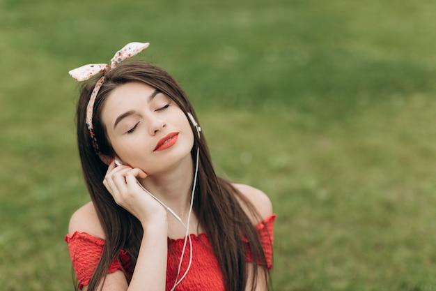 Ritratto del primo piano delle cuffie d'uso della giovane bella donna contenta, ascoltando musica con gli occhi chiusi e trovantesi sull'erba in parco