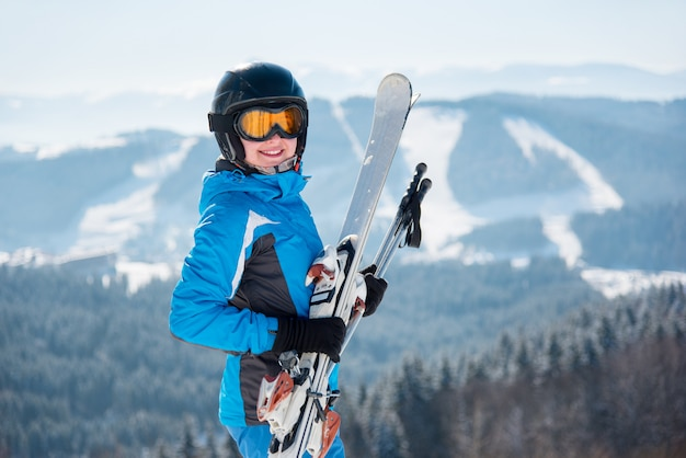 Ritratto del primo piano dello sciatore femminile felice che sorride alla macchina fotografica