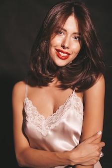 Ritratto del primo piano di bella donna castana sensuale sorridente. ragazza in eleganti abiti classici beige. modello con le labbra rosse isolate sul nero