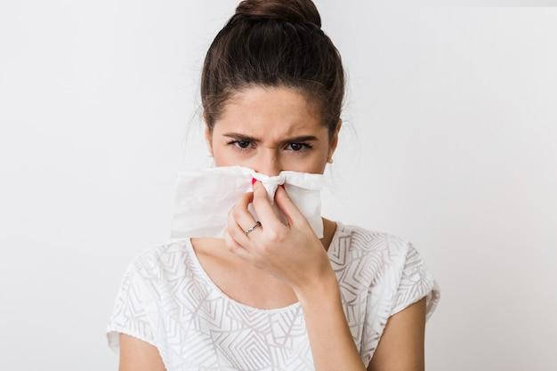 Ritratto del primo piano di bella donna che soffia il naso con il tovagliolo, prendere un raffreddore, sensazione di malessere, isolato, accigliato