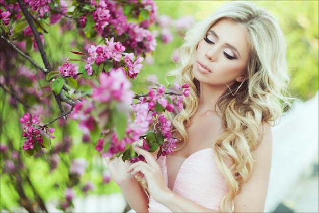 Ritratto del primo piano di bella donna con capelli biondi lunghi in un giardino floreale rosa di estate.