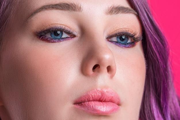 Ritratto del primo piano di bella donna con capelli rosa e le labbra luminose