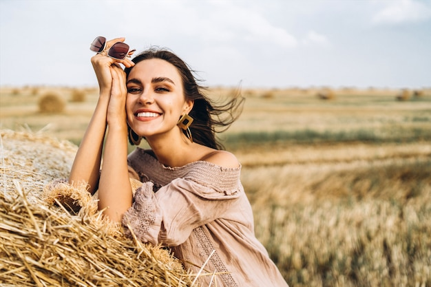 Ritratto del primo piano di bella donna sorridente con gli occhi chiusi. la bruna si appoggiò a una balla di fieno. un campo di grano sullo sfondo