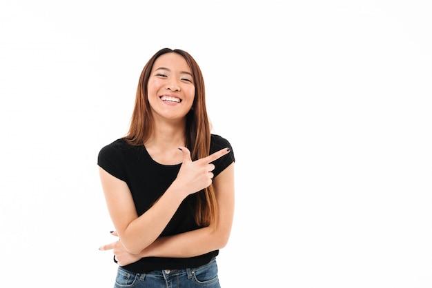 Ritratto del primo piano di bella giovane donna asiatica sorridente che indica con il dito, esaminante macchina fotografica