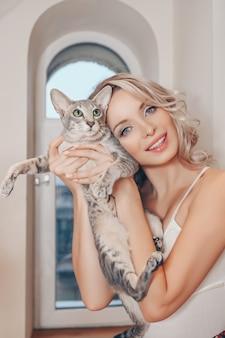 Ritratto del primo piano di bella giovane donna bionda a casa interna e adorabile gatto domestico divertente. sphynx grigio orientale pelo corto peterbald con occhi verdi e orecchie grandi. concetto di persone e animali