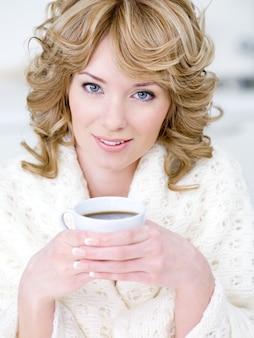 Ritratto del primo piano di bella giovane donna che tiene tazza di caffè