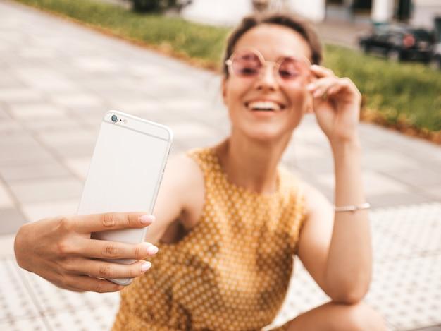 Ritratto del primo piano di bella ragazza castana sorridente in vestito da giallo dei pantaloni a vita bassa di estate. selfie di presa di modello sullo smartphone donna che fa le foto nella calda giornata di sole in strada in occhiali da sole