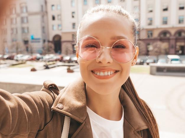 Ritratto del primo piano di bella ragazza sorridente del brunette in rivestimento dei pantaloni a vita bassa di estate. selfie di presa di modello sullo smartphone.