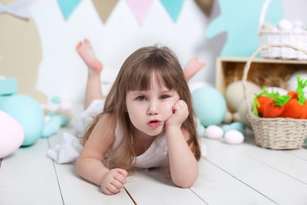 Ritratto del primo piano di bello fronte della bambina. molte colorate uova di pasqua, colorate decorazioni interne di pasqua. coniglietto di pasqua, carota e bandiere colorate. il bambino si risente e aggrotta le sopracciglia. emozioni del bambino.