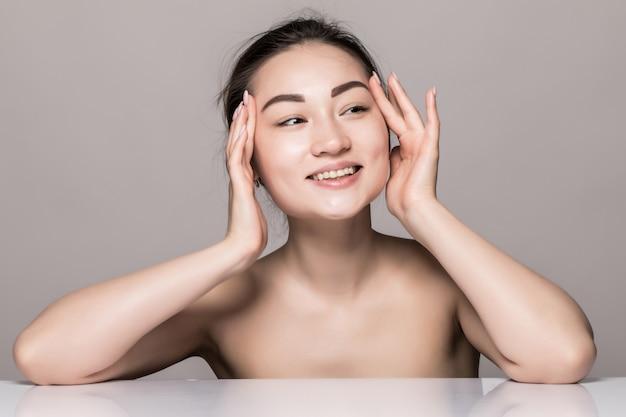 Ritratto del primo piano di cura di pelle del fronte della giovane donna con i cosmetici isolati sulla parete grigia