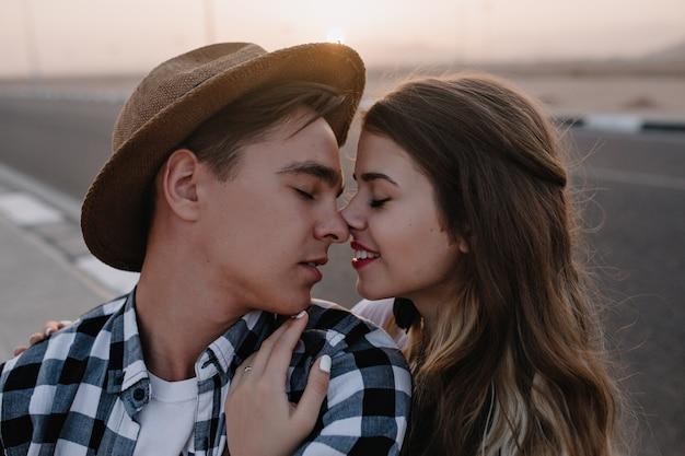Ritratto del primo piano di due persone innamorate, toccando il naso e in posa con gli occhi chiusi al tramonto. graziosa donna bruna trascorrere del tempo con il suo fidanzato in cappello alla moda in posa su appuntamento romantico all'esterno