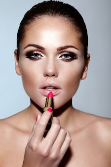 Ritratto del primo piano di fascino di bello modello sexy giovane donna caucasica del brunette che applica rossetto di trucco sulle sue labbra con pelle pulita perfetta