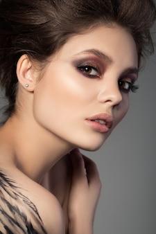 Ritratto del primo piano di giovane bella donna castana con bodyart ala nera sulla sua spalla