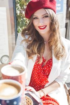 Ritratto del primo piano di giovane bella donna che indossa berreto rosso.