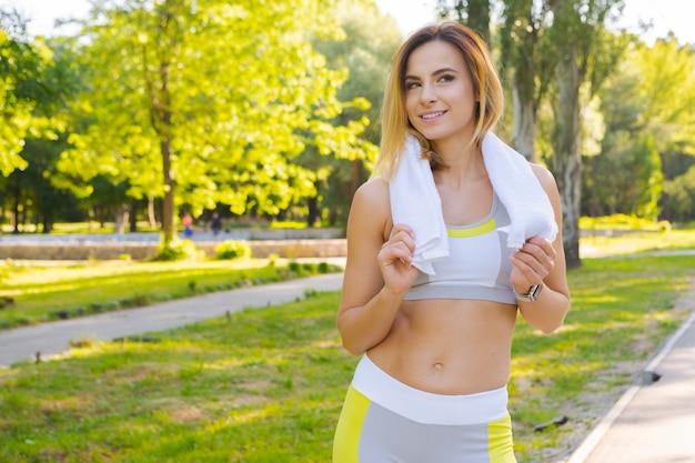 Ritratto del primo piano di giovane bella donna di sport nel parco di estate