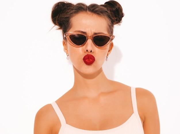Ritratto del primo piano di giovane bella donna sexy dei pantaloni a vita bassa con le labbra rosse in occhiali da sole.