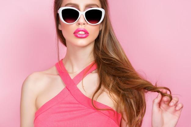 Ritratto del primo piano di giovane bella giovane donna sexy esile in vestito sexy con le labbra sensuali rosse sugli occhiali da sole da portare rosa. sorridente e in posa