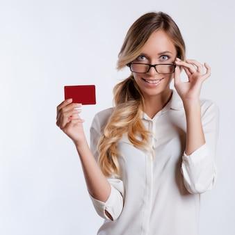 Ritratto del primo piano di giovane carta di credito sorridente della tenuta della donna di affari isolata su fondo bianco