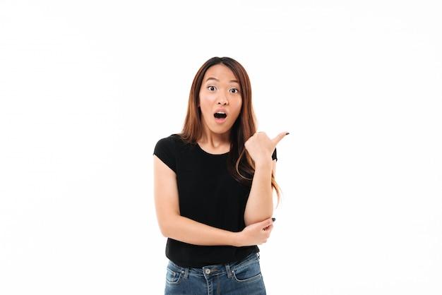 Ritratto del primo piano di giovane donna abbastanza asiatica colpita che mostra pollice sul gesto, esaminante macchina fotografica