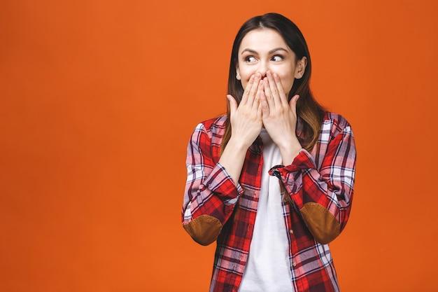 Ritratto del primo piano di giovane donna abbastanza sorpresa con la bocca aperta che sta con le palme aperte, isolato su fondo arancio.