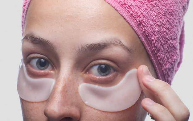 Ritratto del primo piano di giovane donna con le toppe bianche sotto gli occhi e l'asciugamano rosa sulla sua testa isolata sul blu. cura della pelle