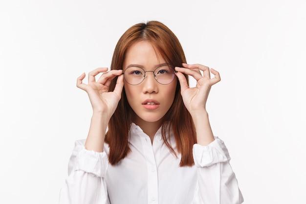 Ritratto del primo piano di giovane donna di affari asiatica dall'aspetto serio che prova sui nuovi occhiali prescritti, prendendosi cura della vista come pick occhiali per lavorare con il computer, in piedi sul muro bianco