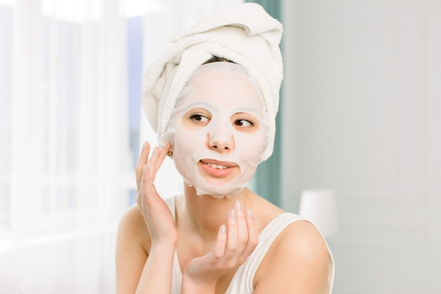 Ritratto del primo piano di giovane donna graziosa che applica la maschera dello strato di carta sul suo fronte. procedura cosmetica. beauty spa e cosmetologia.