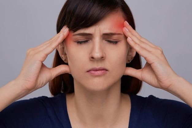 Ritratto del primo piano di giovane donna su fondo grigio che soffre dal forte mal di testa
